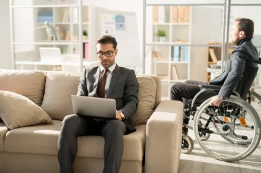 Serious manager in suit sitting on sofa and typing on laptop with disabled businessman moving around the office in wheelchair in the background