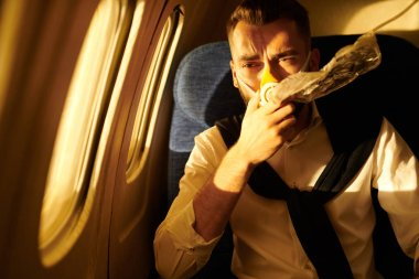 Portrait of handsome young man wearing oxygen mask in plane, copy pace