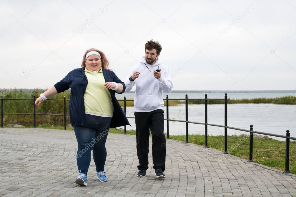 Full length portrait of overweight woman running outdoors with personal trainer motivating her, copy space