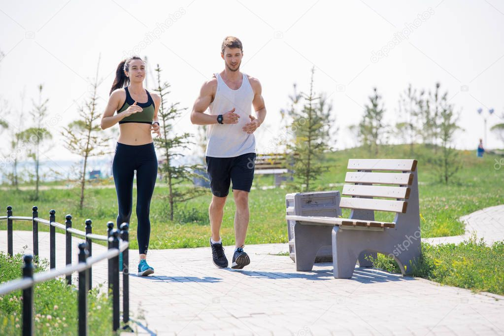 Full length portrait of modern young couple running together outdoors in park, copy space