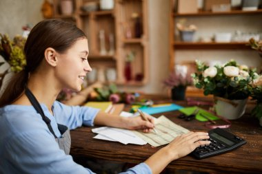 Side view portrait of female businesswoman counting finances using calculator in small shop, copy space
