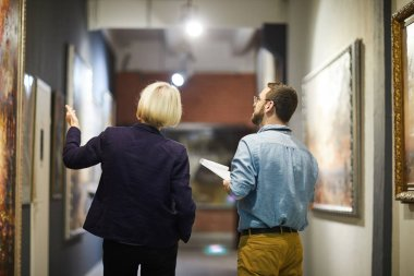Back view portrait of two museum workers discussing paintings walking in art gallery, copy space