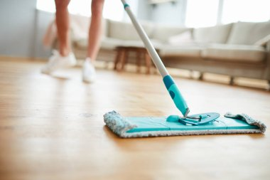 Close-up of unrecognizable woman using mop with microfiber pad while cleaning parquet floor in living room