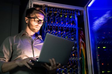 Serious busy young IT engineer in glasses standing against network server equipment with glowing sensors in dark room and using laptop while monitoring network systems