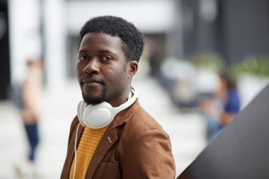 Portrait of serious handsome young black man with wired headphones on neck standing in lobby