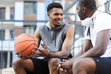 """Картина, постер, плакат, фотообои """"Портрет двух афро-американских парней в чате сидя на баскетбольной площадке на открытом воздухе, копировать пространство"""", артикул 303131484"""