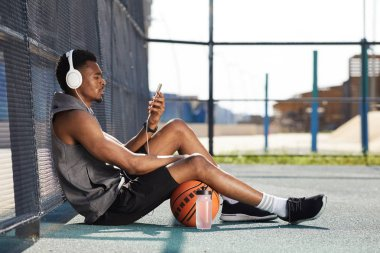 Side view portrait of contemporary African-American man wearing headphones and using smartphone while sitting in basketball court outdoors, copy space