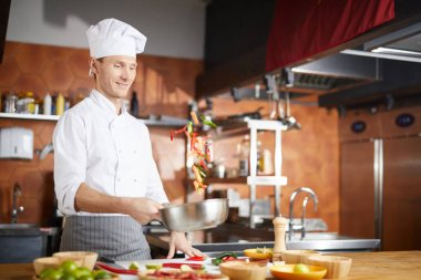 Waist up portrait of handsome chef tossing vegetable while cooking Asian dish in restaurant kitchen, copy space