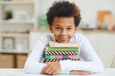 Portrait of cute African-American boy holding books while studying at home and smiling at camera, copy space