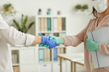 Close up of two people wearing gloves shaking hands while greting each other at work in office, copy space stock vector