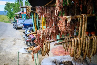 Original Caribbean food on the roadside in the Dominican Republic. Smoked pork, morcillas and longanizas