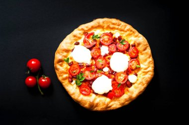 Homemade pizza on black background. The concept of traditional Italian food.