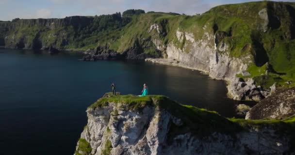 Rocky sea shore, photoshooting on top of a cliff with turquoise long dressed model at sunrise at Kinbane Castle, in Antrim coast, North Ireland