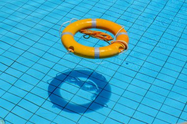 Lifebuoy floating on top of sunny blue water in swimming pool, close up