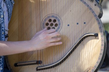 Ukrainian girl playing the harp on the street of Kyiv for passersby, Ukraine, close up
