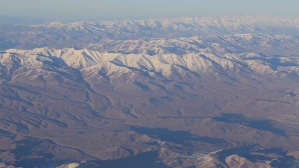 Aerial views in mountain. View from the plane window. The Hindu Kush mountain system in Afghanistan. Top view