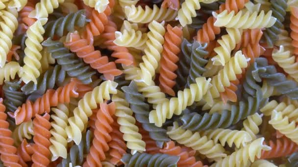 Multicolored pasta background, rotating, top view. Rotation of colored spiral pasta. Heap of uncooked pasta. Italian food close up. Delicious italian fusilli, tricolor pasta, food background