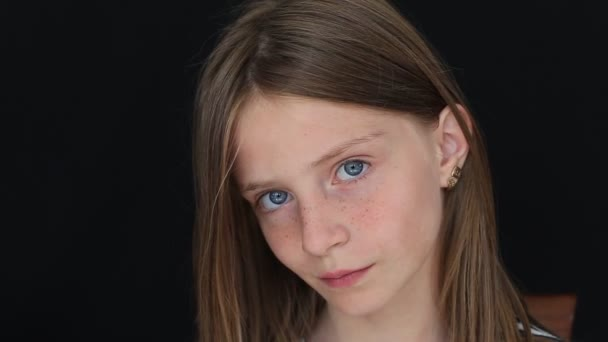 Beautiful blond young girl with freckles indoors on a black background, close up portrait