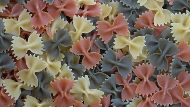 Multicolored pasta background, rotating, top view. Rotation of colored farfalle pasta. Heap of uncooked pasta. Italian food close up. Delicious italian farfalle tricolor pasta, food background