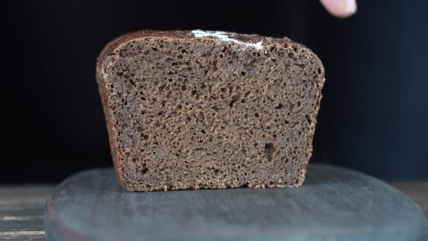 Cutting two slices of brown bread on wooden board. Cut the whole grain bread with a knife. Close up of dark bread, healthy lifestyle.