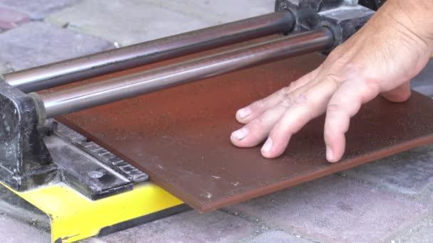 Piastrellista con una tagliapiastrelle manuale taglia mattonelle sul