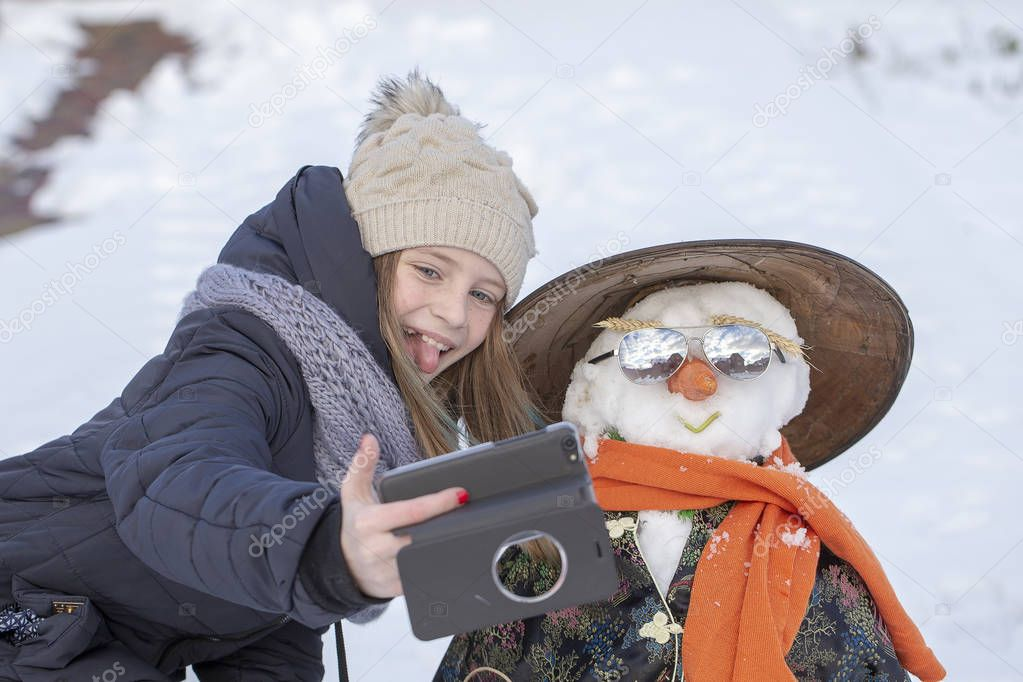 Adorable young girl is taking pictures of selfie with a snowman in beautiful winter park. Winter activities for children. Close up