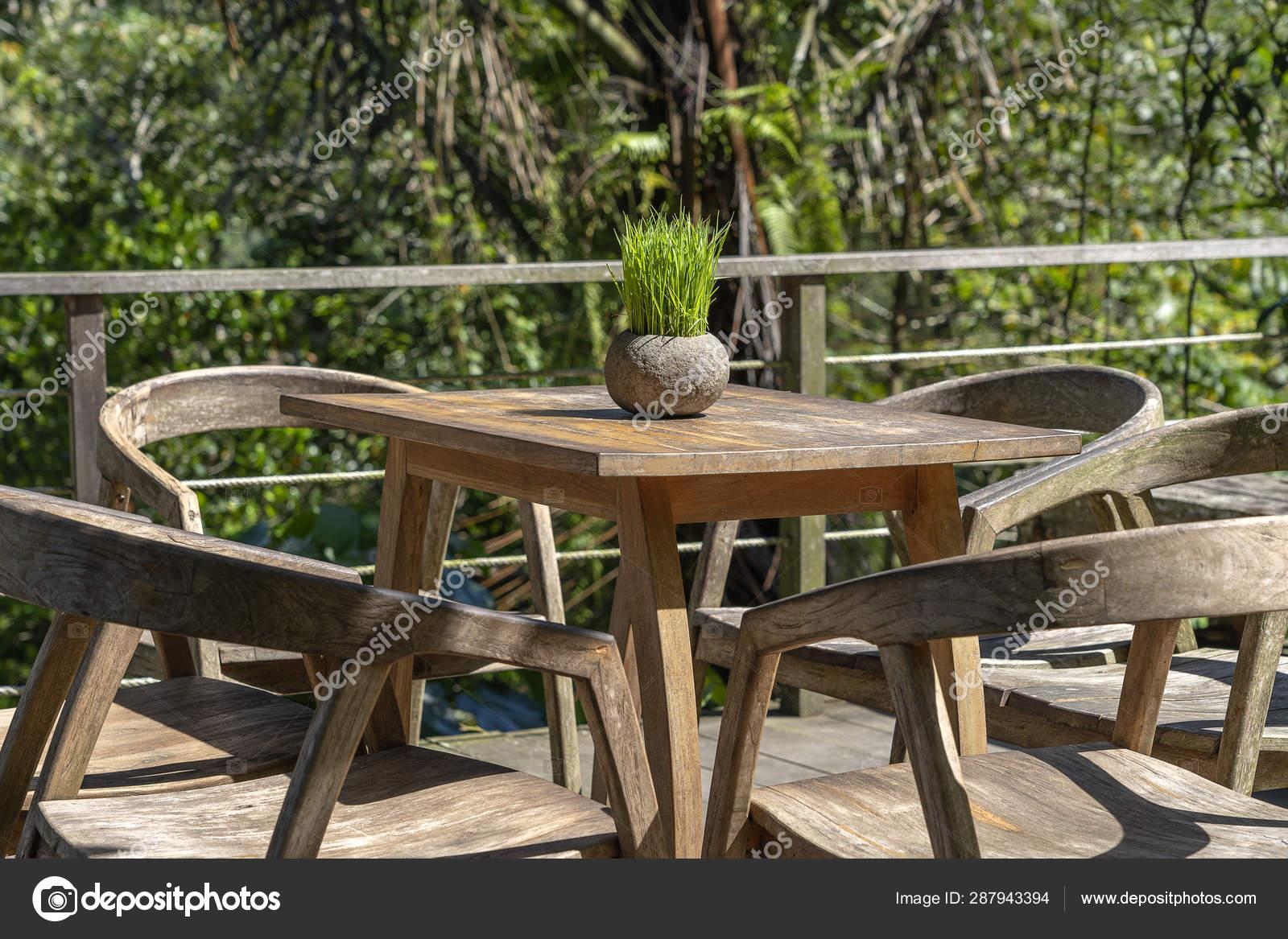 Mesa De Madera Y Sillas En Café Tropical Vacío Junto A