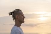 Silhouette eines jungen Kerls mit Dreadlocks auf dem Kopf in der Nähe des Meeres während des Sonnenuntergangs. Nahaufnahme Porträt
