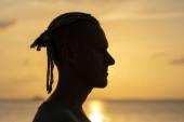 Silhouette eines jungen Mannes mit Dreadlocks auf dem Kopf in der Nähe des Meeres bei Sonnenuntergang. Porträt aus nächster Nähe