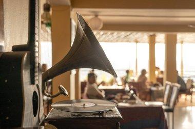 Old gramophone, guitar and people in restaurant, focus on gramophone, closeup