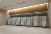 Photo A row of urinals in tiled wall in a public restroom. Empty man toilet