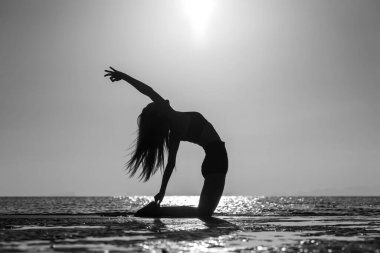 Silhouette of woman standing at yoga pose on the tropical beach during sunset. Caucasian girl practicing yoga near sea water. Black and white stock vector