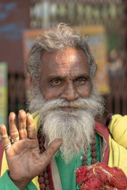 RISHIKESH, INDIA - NOVEMBER 06, 2018 : Portrait of Hindu sadhu holy man, sits on the ghat and asks for alms from passers-by near the Ganges river in Rishikesh, India, close up