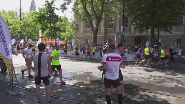 Marathon runners drink water and run on
