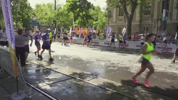 Athletes at the marathon drink water, volunteers help
