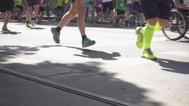 Legs of marathon runners running along the asphalt