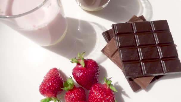 Dva koktejly v brýlích a jahody s čokoládou