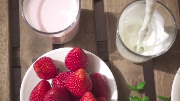 Dvě sklenice s mléčné koktejly a sklenici s tekoucí mléko Zpomalený pohyb