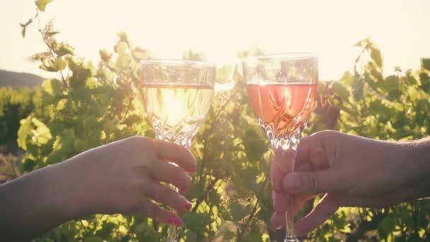 Muž a žena řinčí poháry při západu slunce