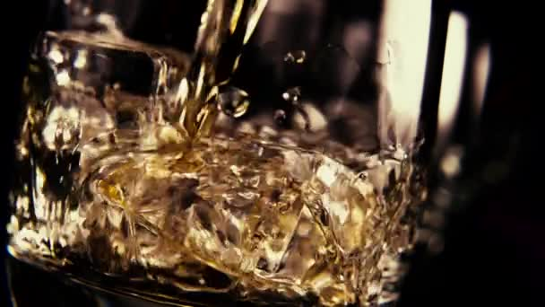 Slow motion pour bourbon into a glass of ice