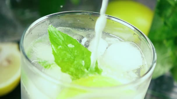 Zpomalený pohyb ve sklenici s ledem mátou a citronovou šťávou