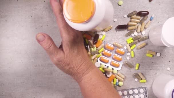 In Zeitlupe verschiebt sich die Hand einer älteren Frau zur Seite der Pille von oben