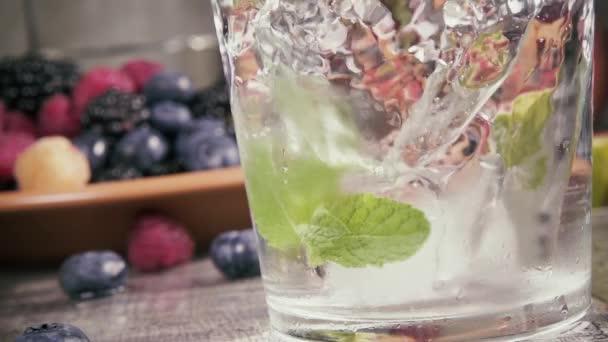Zeitlupe reines Wasser mit Eis auf dem Hintergrund von Beeren
