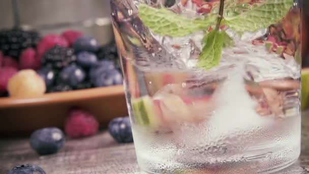 Slow motion in a glass of water and mint ice falls