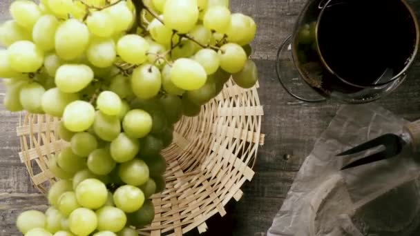 Slow motion a bunch of grapes falls into the basket on the table top view