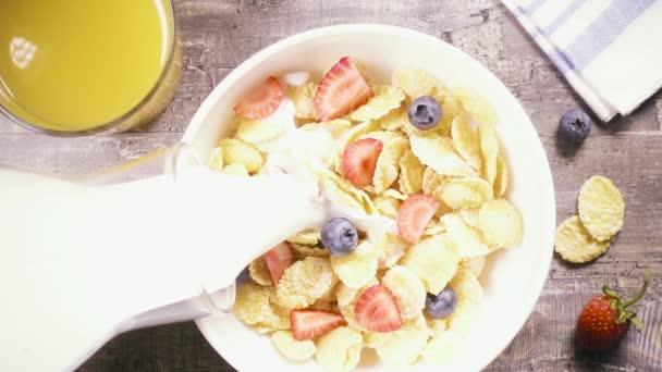 Zpomalený pohyb kukuřičné lupínky s ovocem nalijte tekuté pohled shora