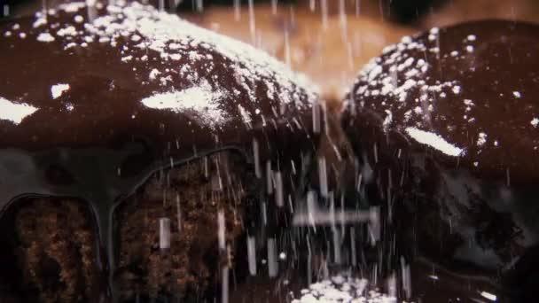 Zpomalený pohyb dva bochánky glazura Kropiti s práškovým cukrem zblízka