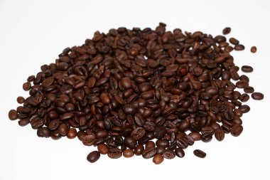 a heap of fresh roasted coffee beans in the white studio