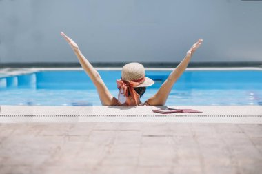 attractive girl with hat back to back in the pool arms raised
