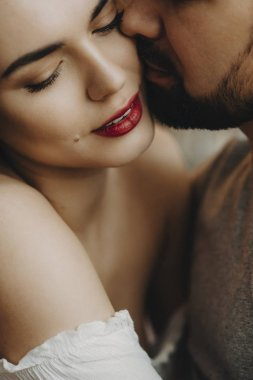 Close up portrait of a beautiful caucasian couple where bearded man is trying to kiss her cheerful wife with red lips.